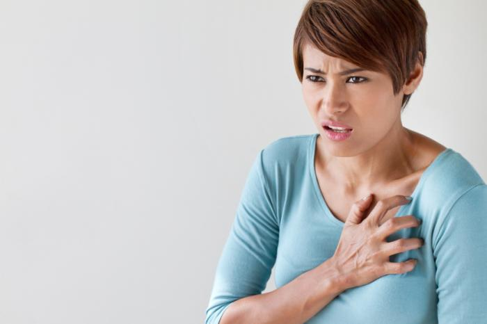 Một người phụ nữ đang ôm ngực mình trong sự khó chịu.