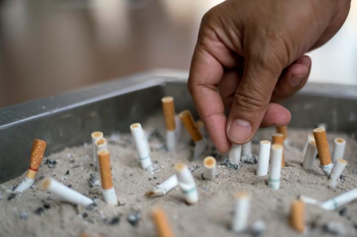 tay cầm một điếu thuốc giữa các hốc trong khay cát