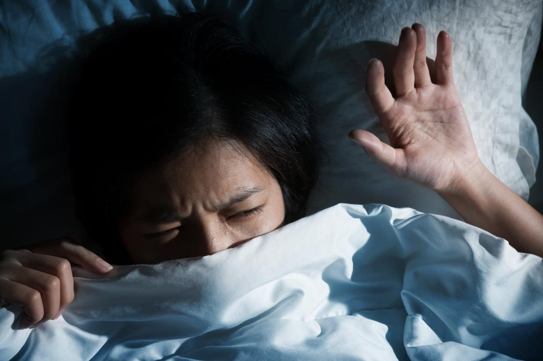 erschrockene Frau im Bett