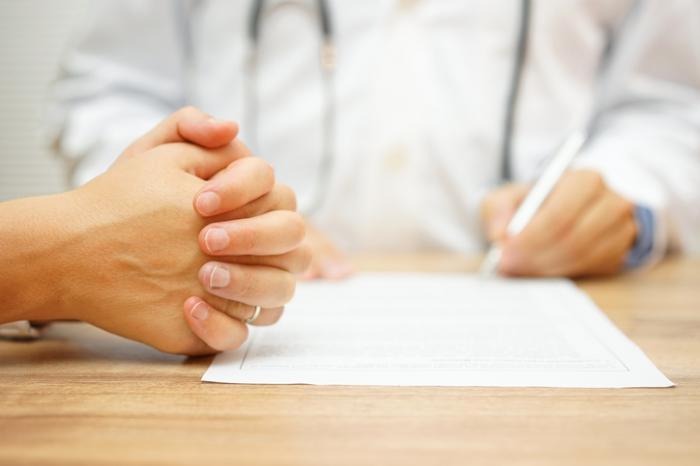 Docteur écrit des notes tandis que le patient serre les mains ensemble