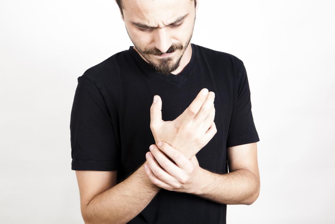 човек, който държи болезнена дясна китка