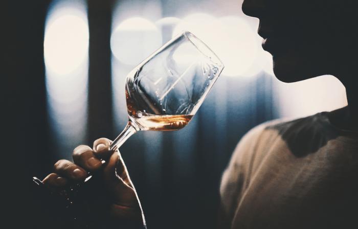 [Uma mulher bebendo um copo de vinho]
