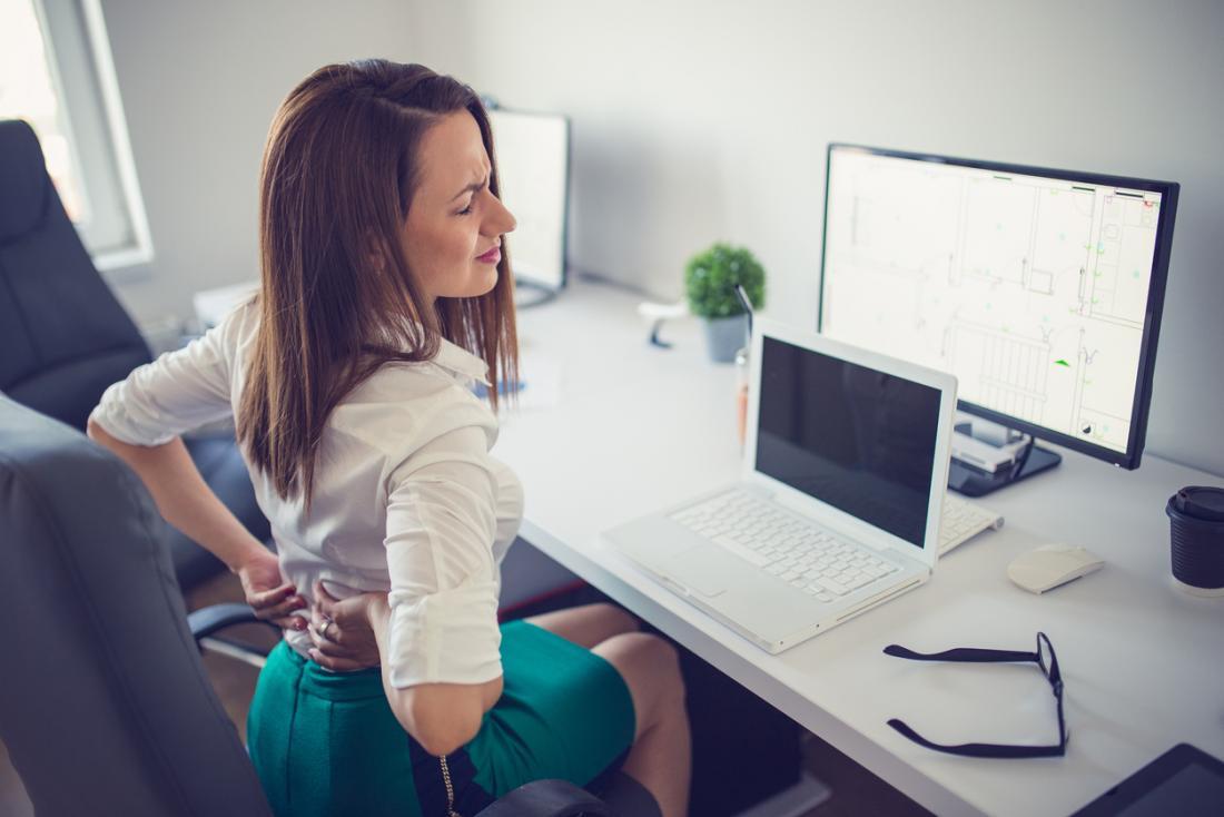 Femme avec des douleurs au bas du dos assis au bureau.