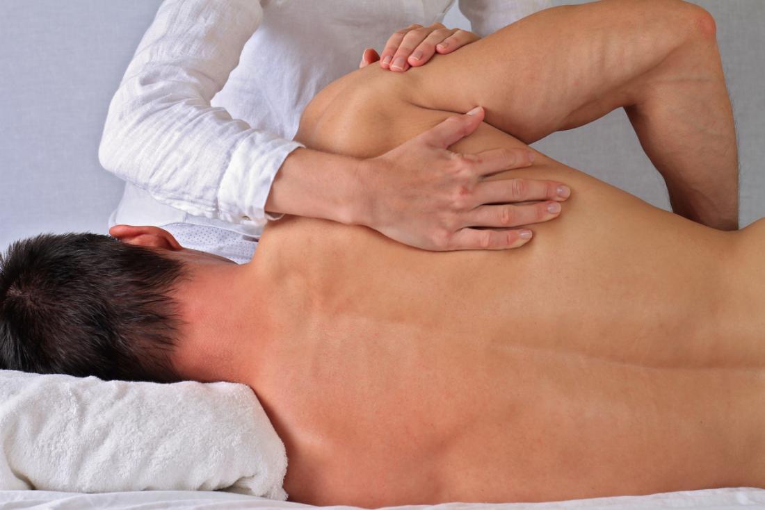 Човек, подложен на физическа терапия на гърба си.
