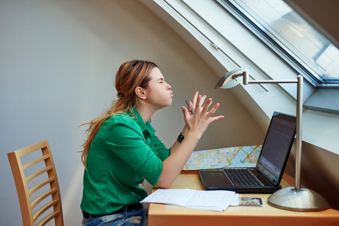 người phụ nữ khó chịu ở bàn làm việc