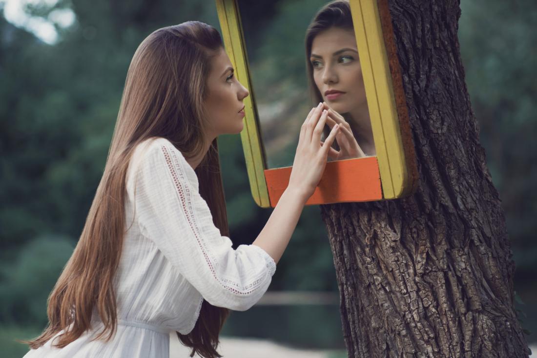 kobieta patrzy na siebie w lustrze