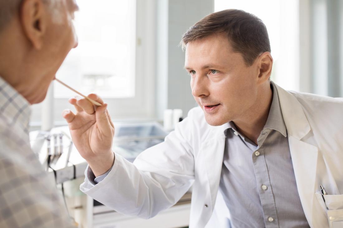 Lekarz sprawdzający usta i język pacjenta.