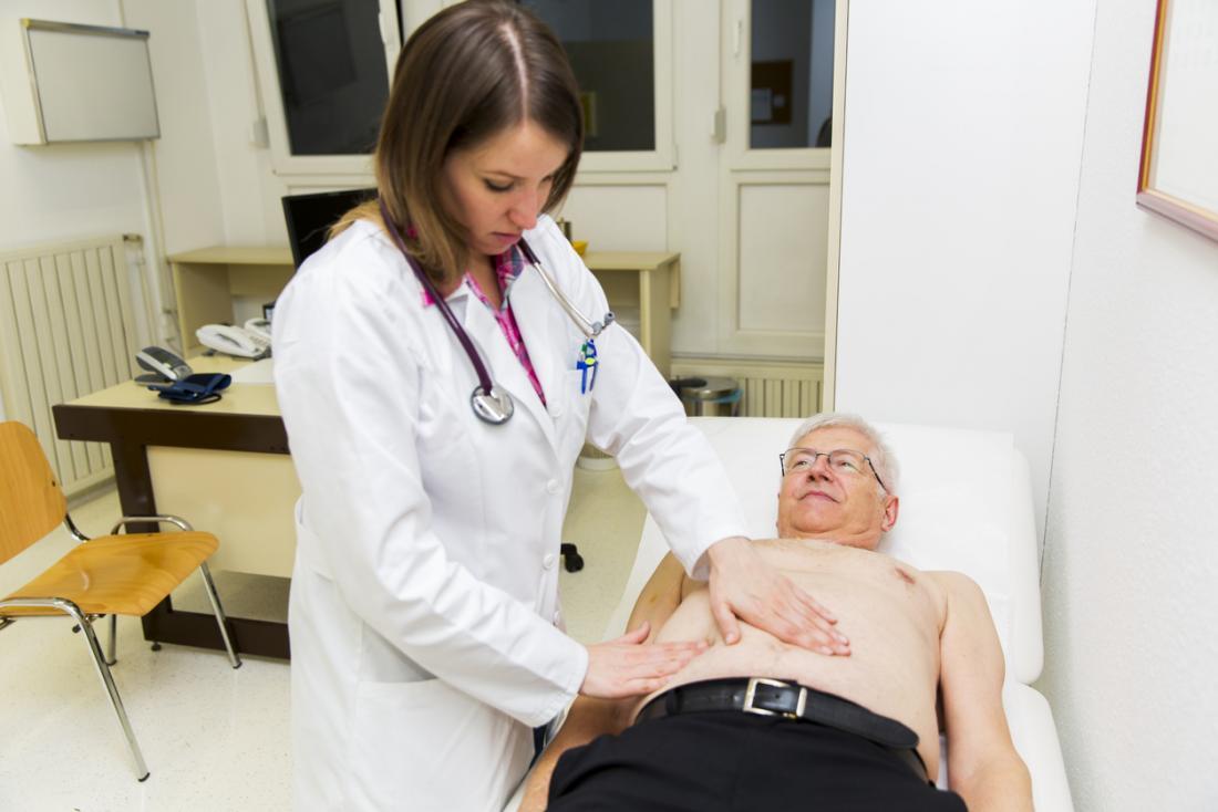 Kıdemli erkek hasta doktordan karın muayenesine sahip.
