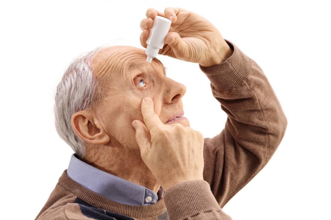 älterer Mann, der Augentropfen in sein Auge setzt