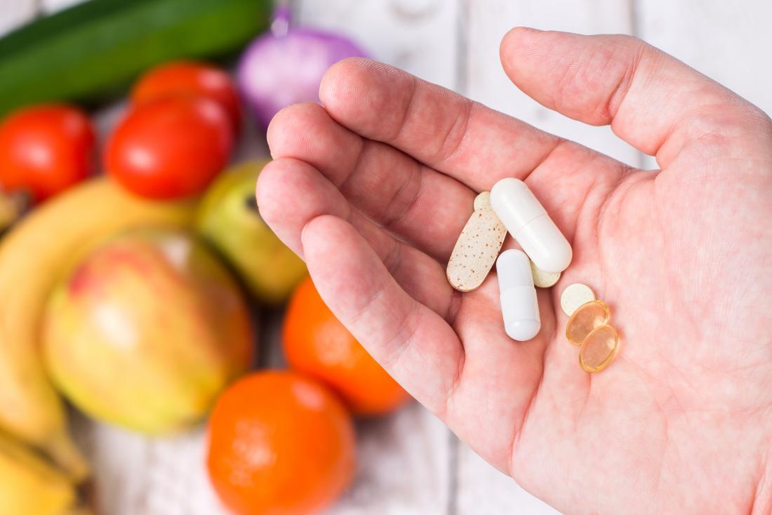 Persona che tiene integratori di vitamine liposolubili su serie di frutta e verdura.