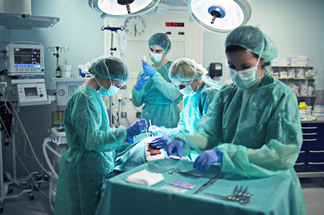 Хирурзи, работещи в операционната, с оборудване и машини във фонов режим.