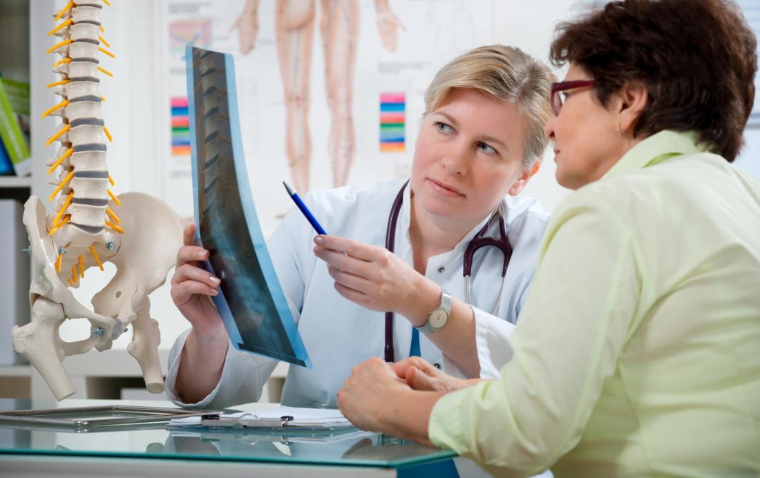Kręgarz i pacjent patrząc na RTG kręgosłupa, obok modelu kręgosłupa.