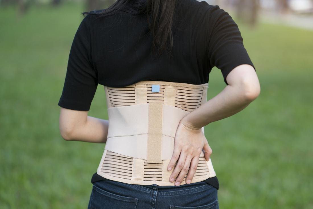 Kobieta noszenia klamry pleców do wsparcia mięśni i postawy kręgosłupa.