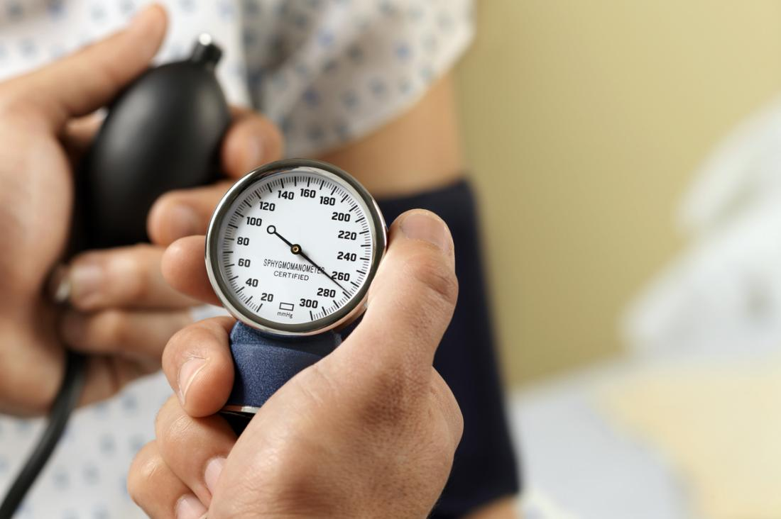 Krankenschwester, die Blutdruck der Patienten mit einer Armpumpe misst.