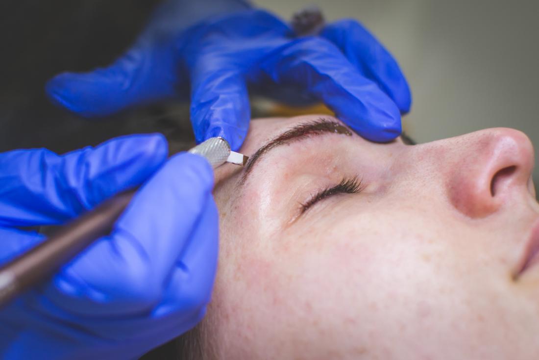 Procedura di tatuaggio cosmetico microblading per le sopracciglia.