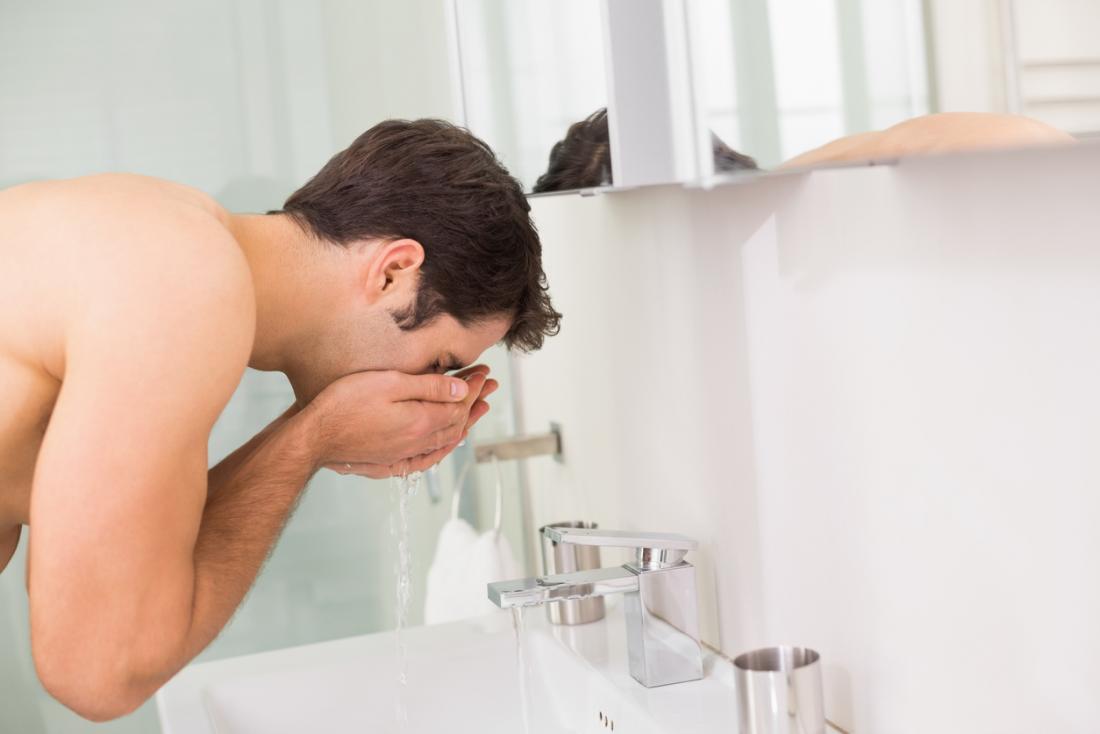 Uomo che si lava delicatamente la faccia con acqua dal lavandino del bagno.