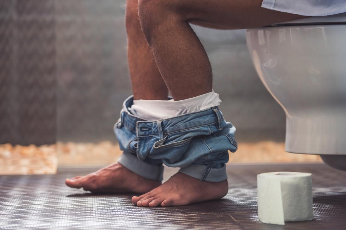 Homem sentado no vaso sanitário.