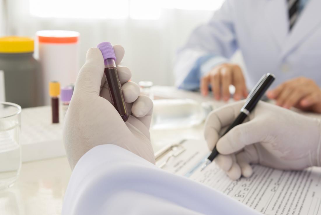 Phlébotomiste examinant la fiole avec l'échantillon d'essai de sang, et remplissant la forme.