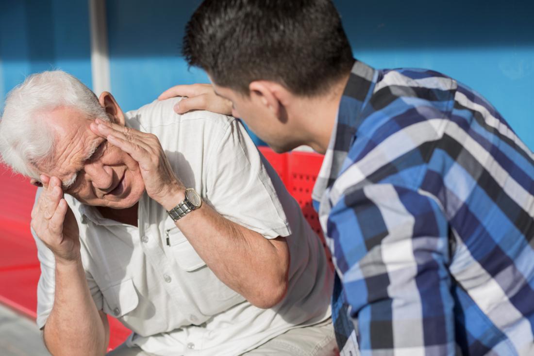 Starszy mężczyzna cierpiący na zawroty głowy, ból głowy i zmęczenie.