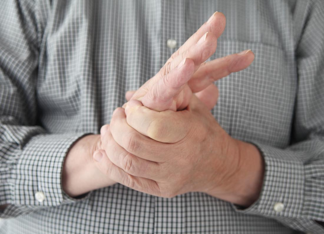 Mann, der Hände hält, während Taubheit und Kribbelngefühl wegen der Neuropathie und der Nervenschädigung erfahren.