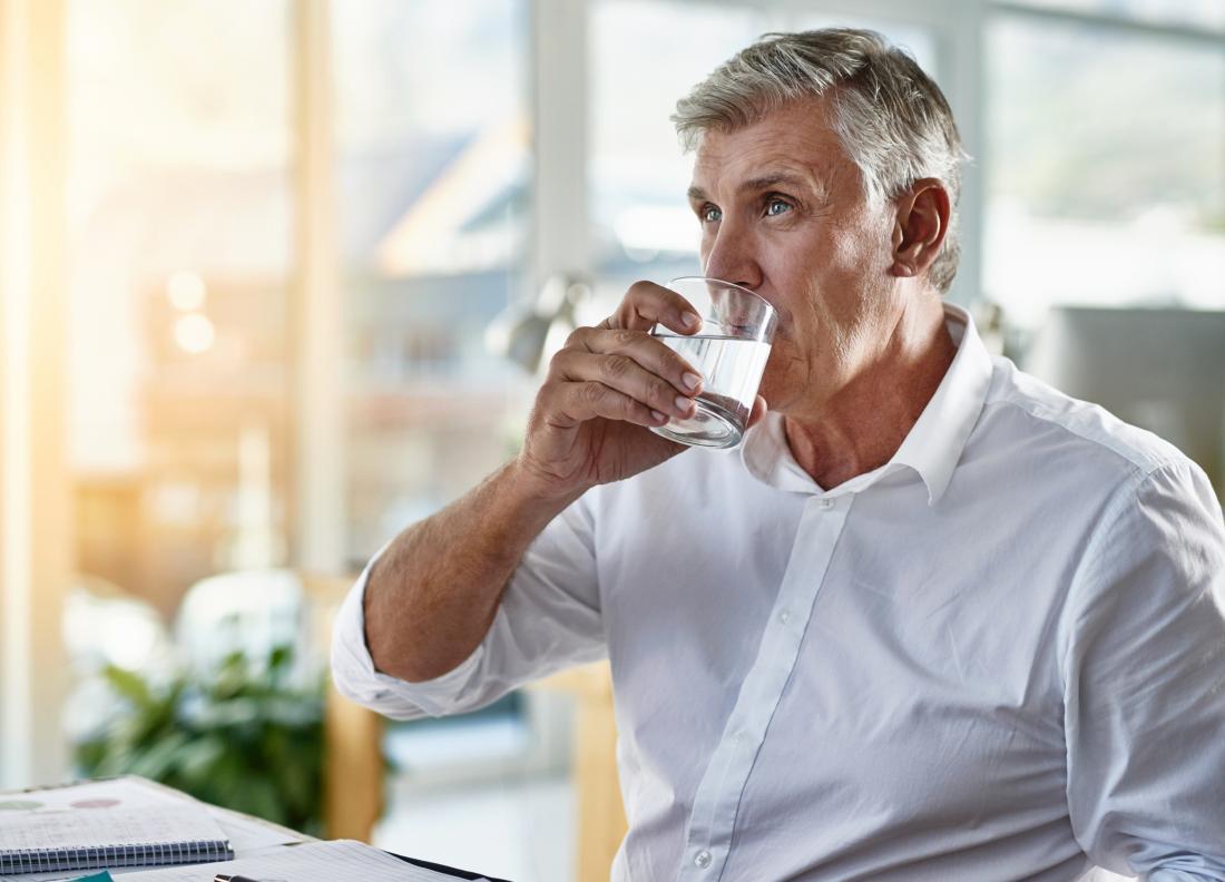 старши човек пиеше чаша вода