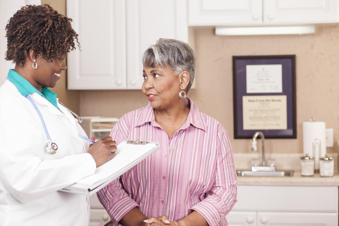 Dojrzały pacjent mówiąc do żeńskiej lekarz,