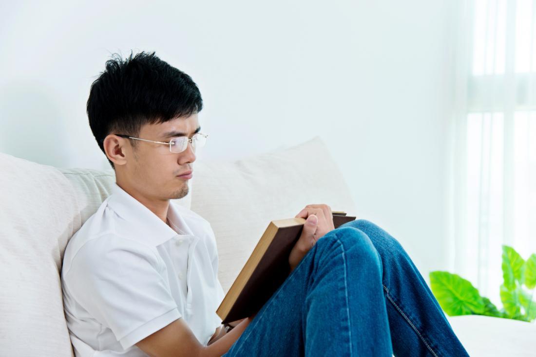 Homem asiático novo que lê em casa.