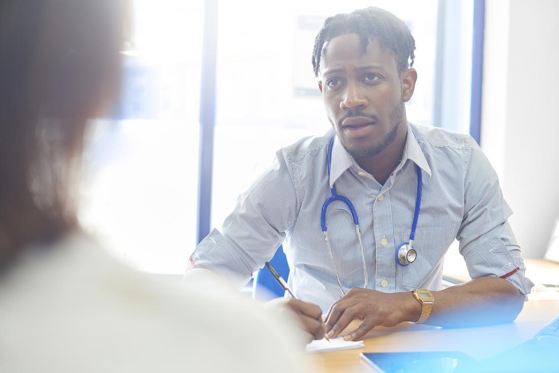 Лекарят говори на пациента за рецепта и състояние.