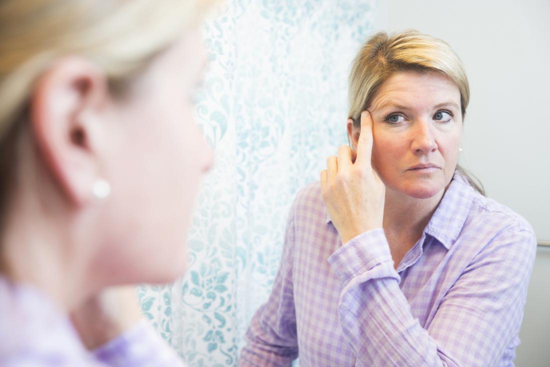 Aynada gözleri ve yüz cildi kontrol kadın.