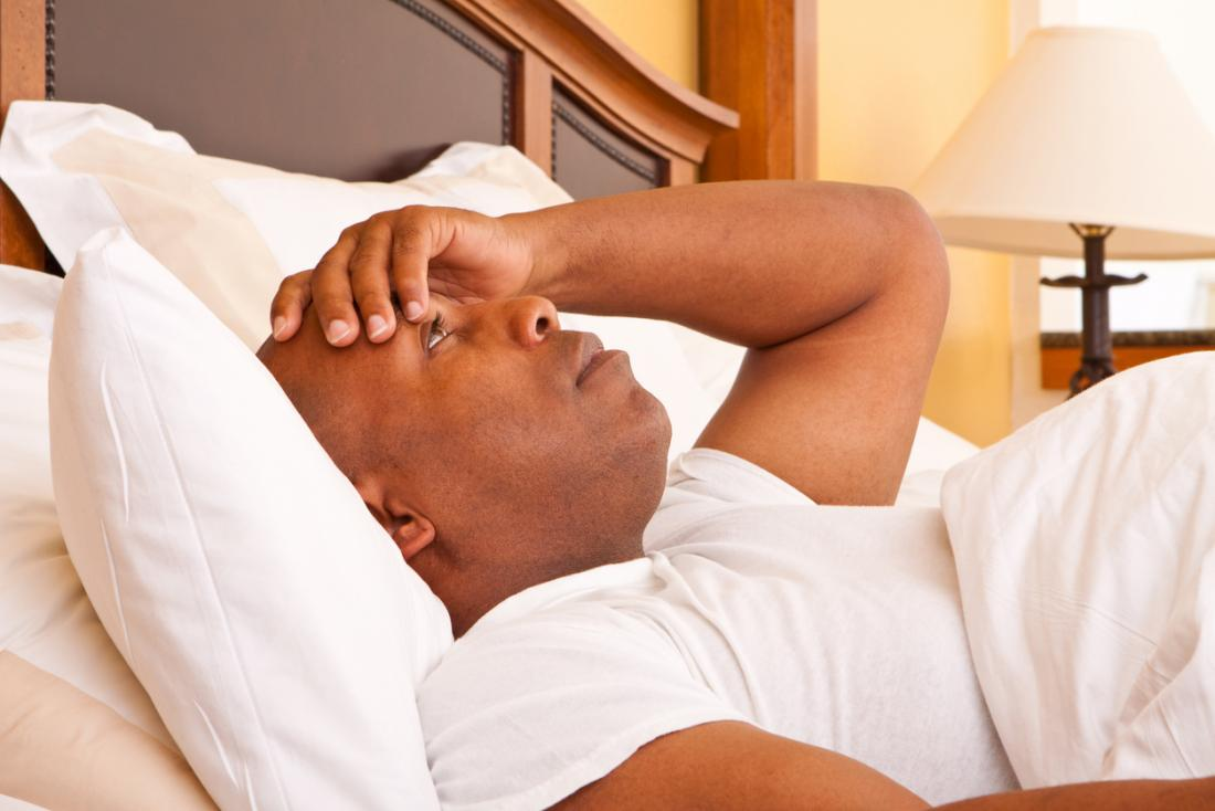 Uykusuzluk ve zayıf uykudan muzdarip adam, yatakta uyanık yatıyor.