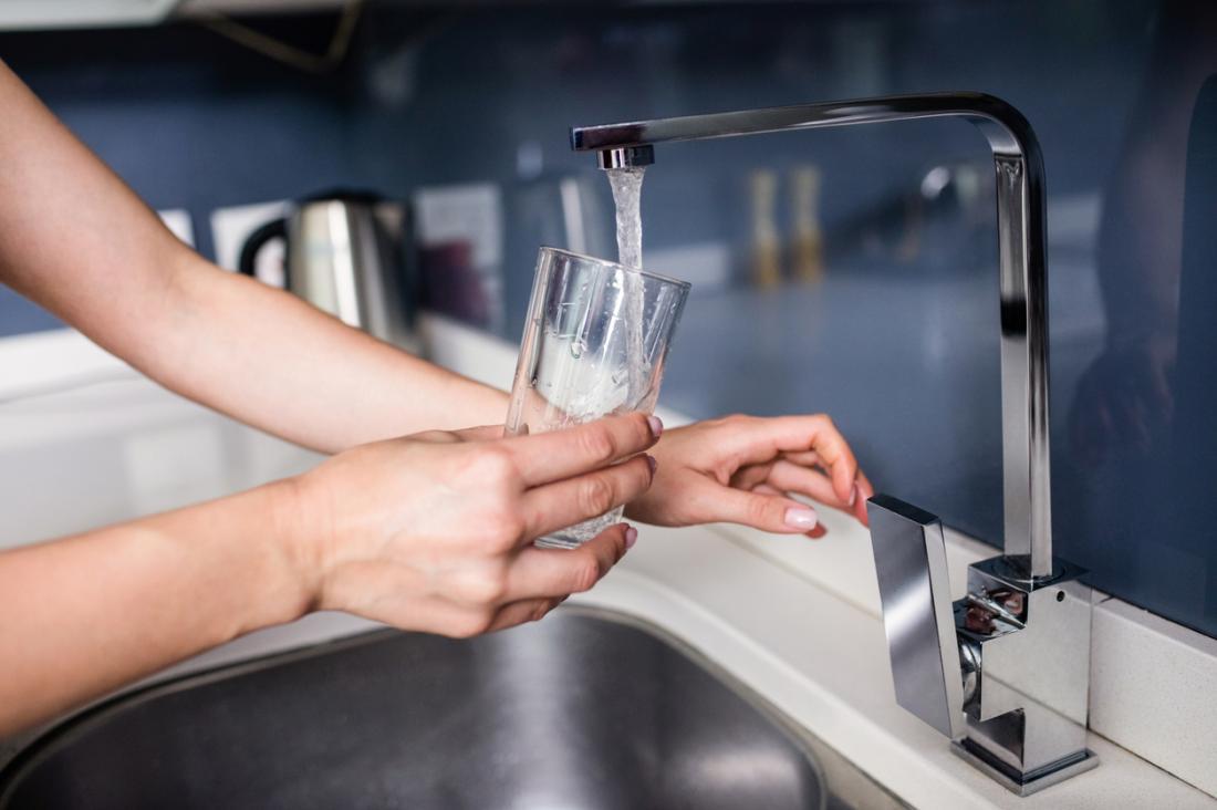 Mutfak musluk suyu cam içine dökerek kişi.