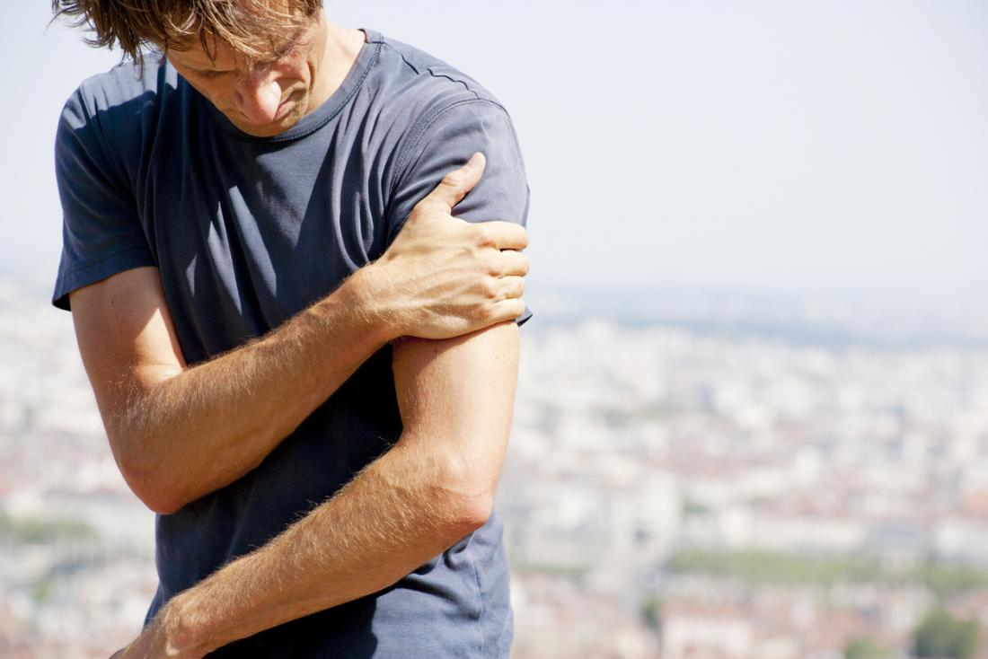 腕と肩に痛みを持つ男。