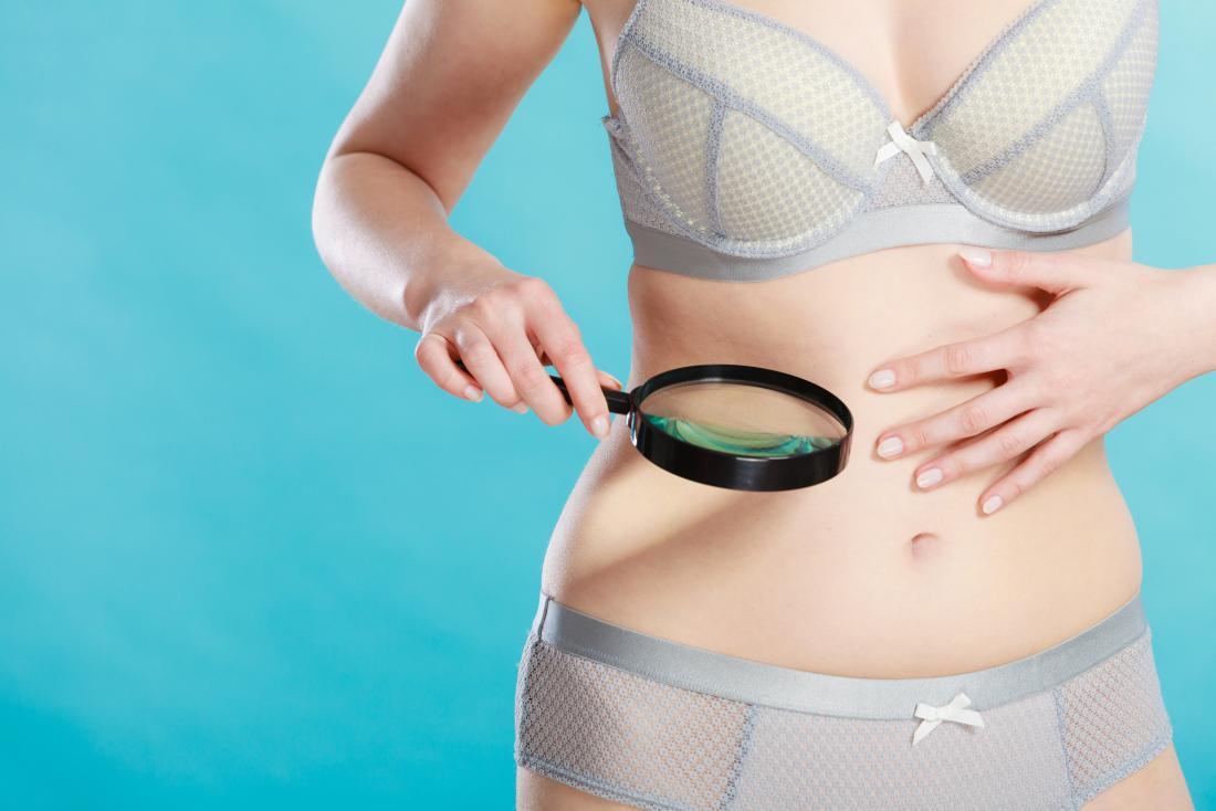 người phụ nữ sử dụng kính lúp để kiểm tra da