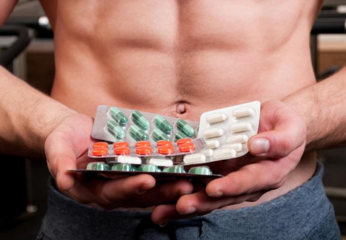 Pessoa muscular segurando drogas.