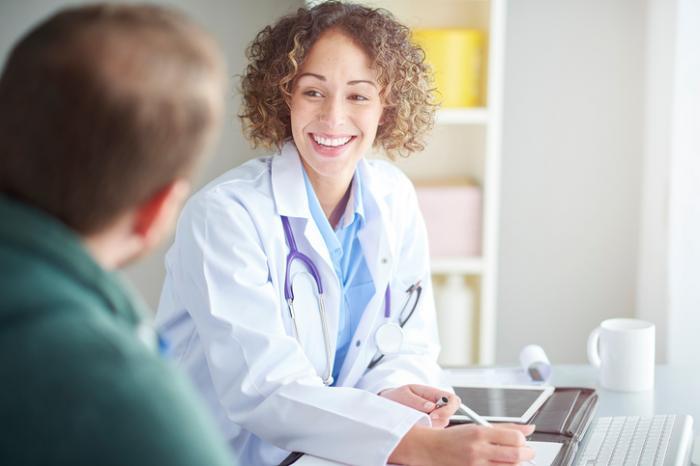 [Kobieta lekarz śmieje się z pacjentem]