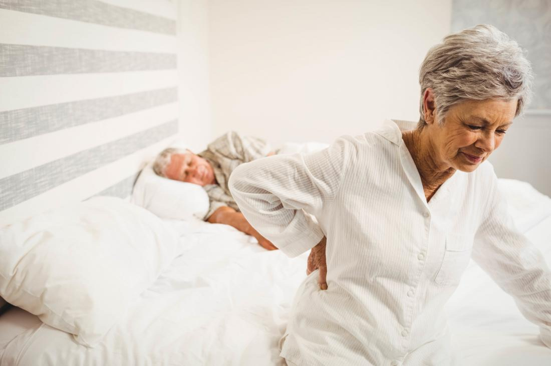 [ältere Frau mit Rückenschmerzen am Morgen]