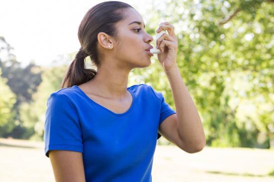 Donna con asma utilizzando inalatore all'esterno