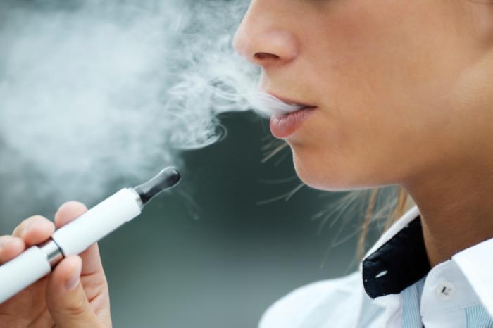 Bir e-sigara kullanan kadın.