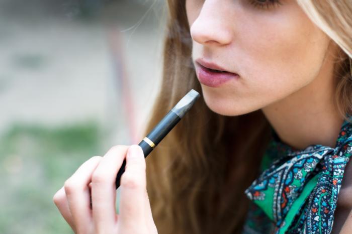 Bir e-sigara kullanan genç bir kız.