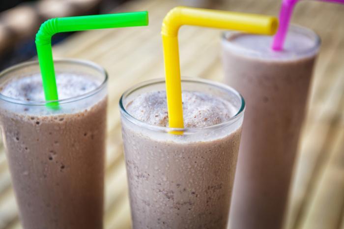 três shakes de proteína em copos com canudos