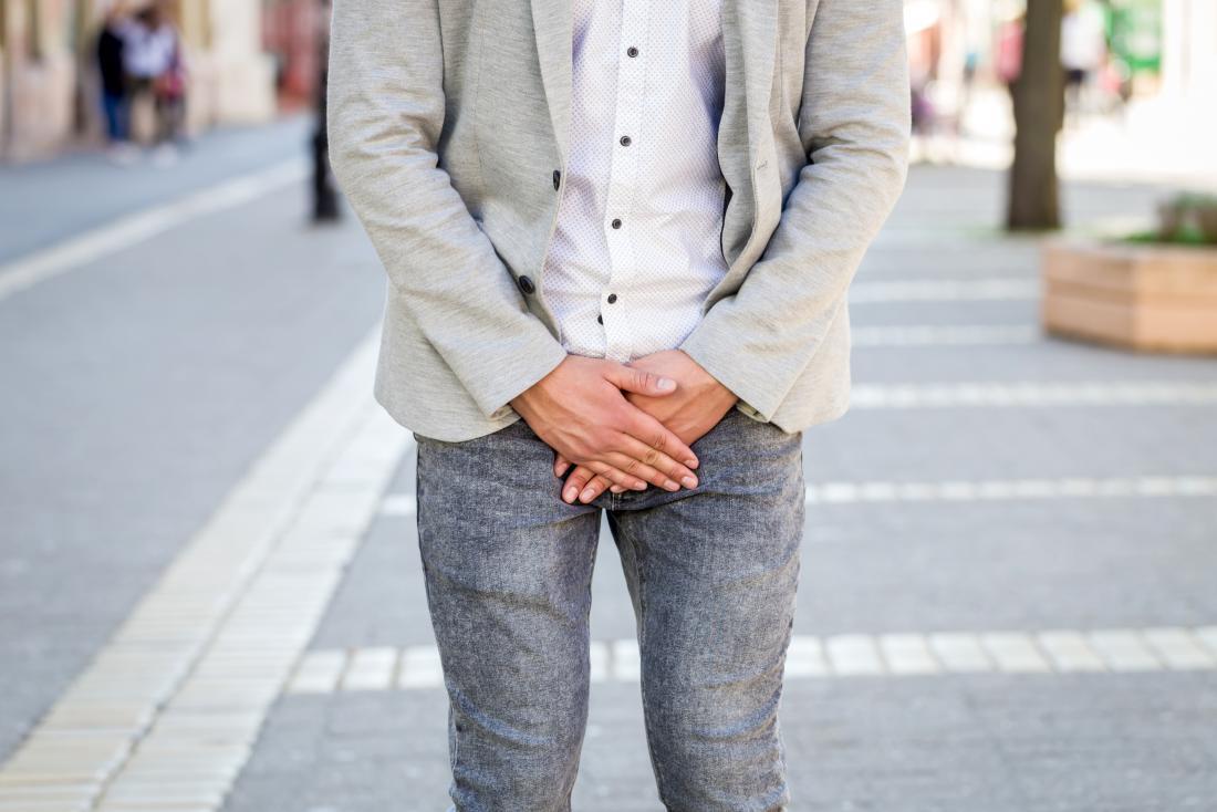 Mann mit der gelegentlichen Aufrichtung, die draußen seinen Schritt mit seinen Händen bedeckt.