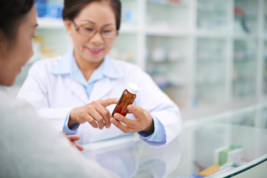 Dược sĩ đọc nhãn trên chai thuốc.