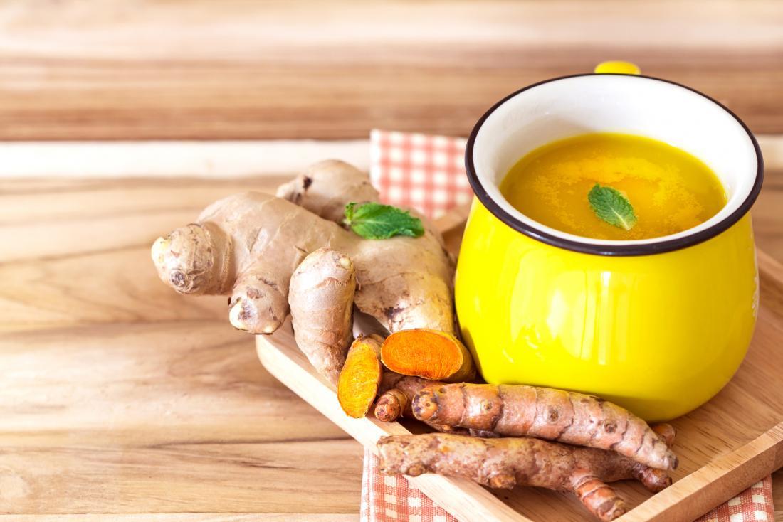 Kupa bitkisel çay ile ahşap tahta üzerinde zerdeçal ve zencefil kökleri.