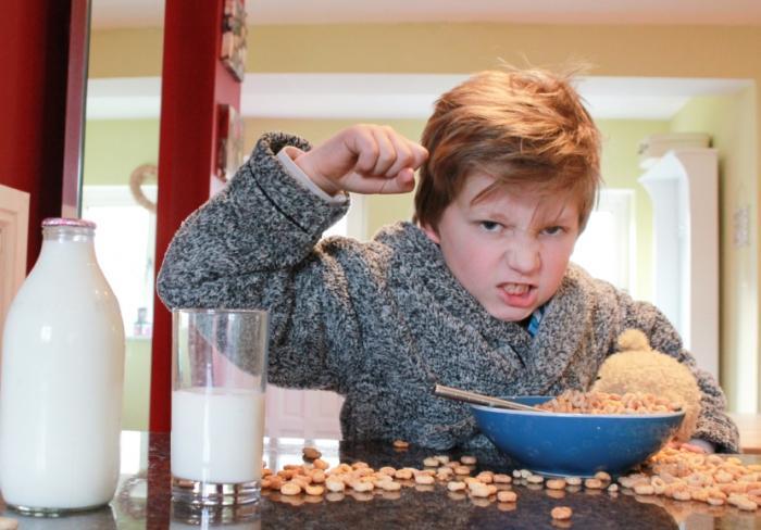 Dziecko robi bałagan z płatków śniadaniowych.