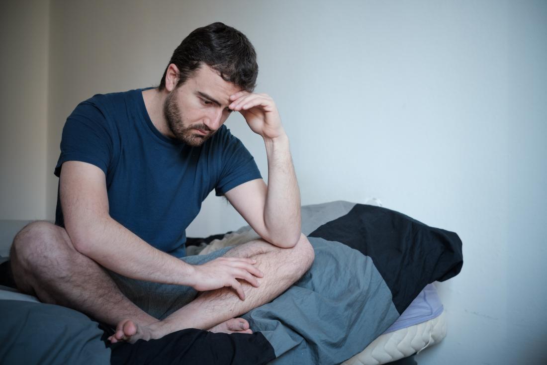 Uomo depresso e ansioso seduto a gambe incrociate sul letto.