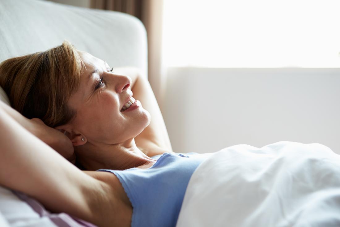 Donna anziana felice a letto la mattina.