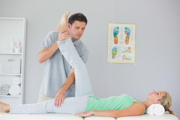 Un fisioterapista allunga la gamba di una donna.