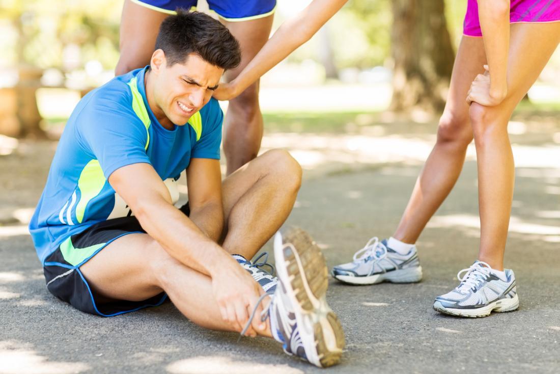 Homem correndo kit sentado segurando seu tornozelo de dor, enquanto outros corredores atendê-lo.