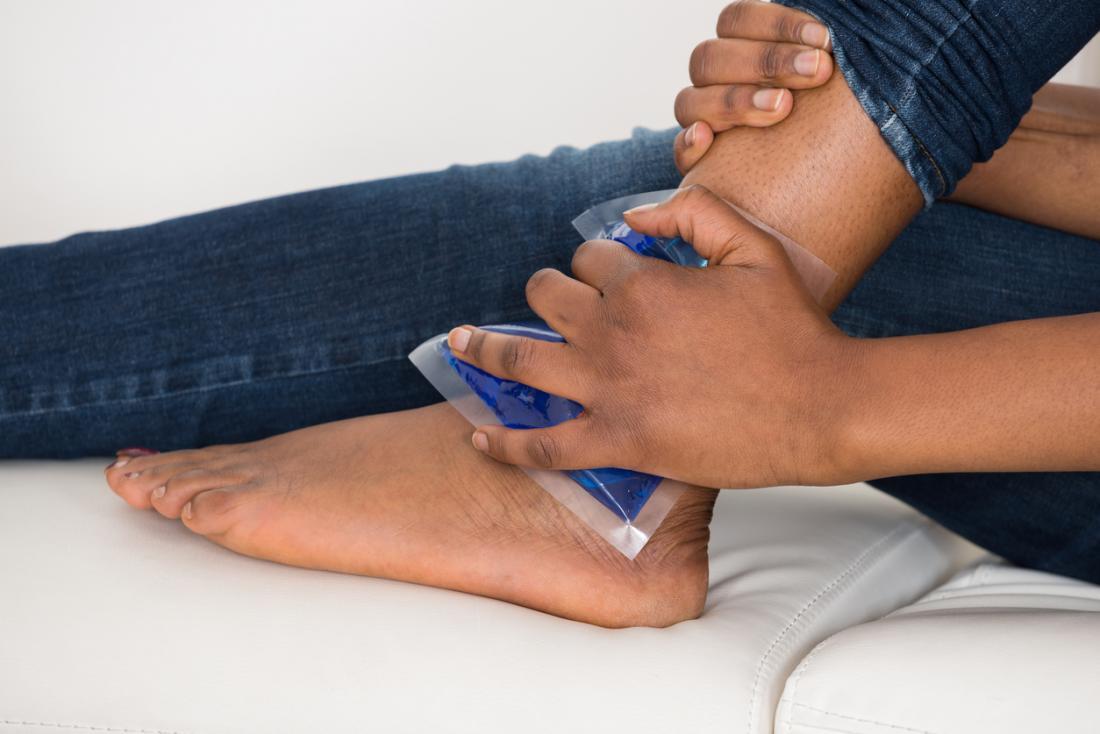 Tornozelo lesionado sendo tratado com uma compressa de gelo na pele.