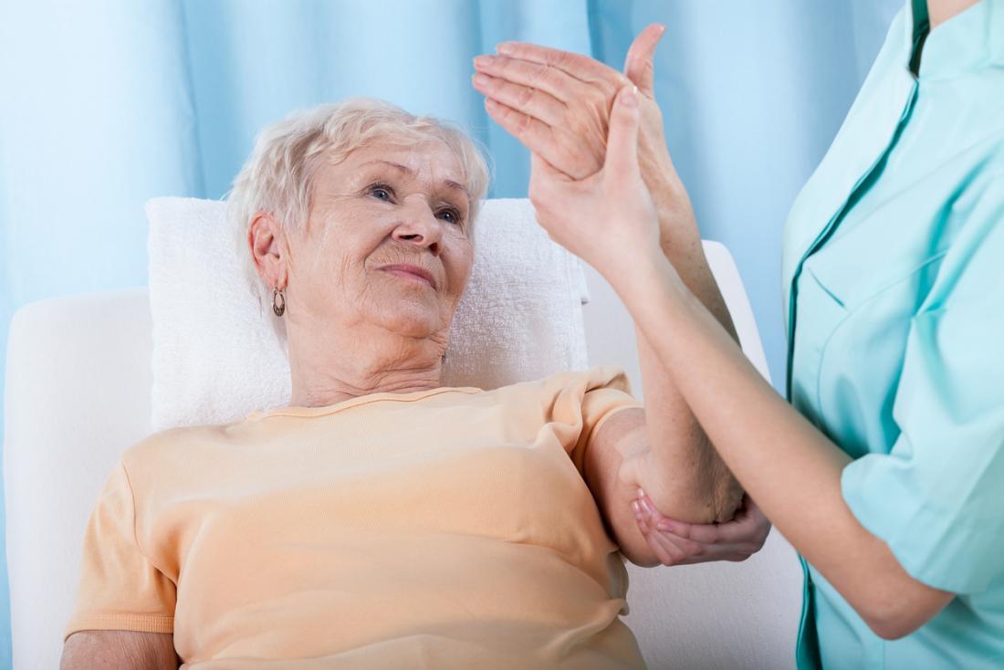Người phụ nữ cao cấp có cánh tay di chuyển bởi y tá.